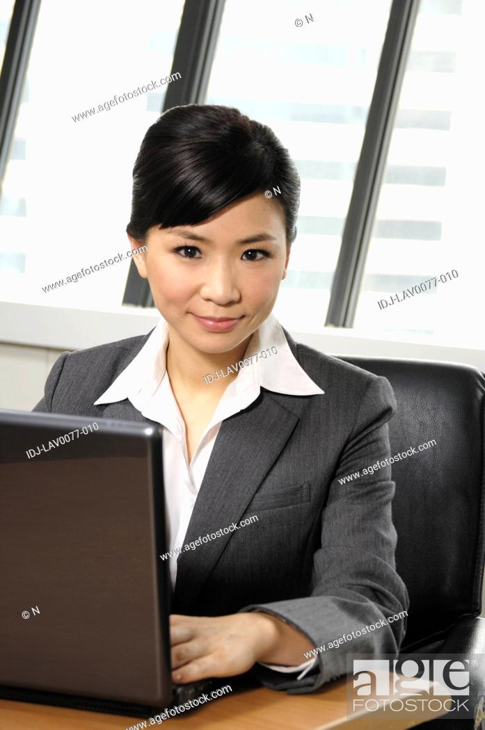 Stock Photo: Businesswoman using a laptop in an office.