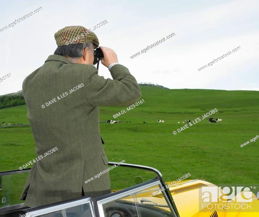 Stock Photo: Man standing in car looking at countryside with binoculars.