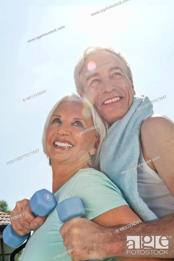 Stock Photo: Germany, Bavaria, Man and woman exercising in garden, smiling.