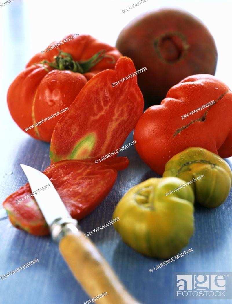 Stock Photo: Tomatoes, one sliced with paring knife.