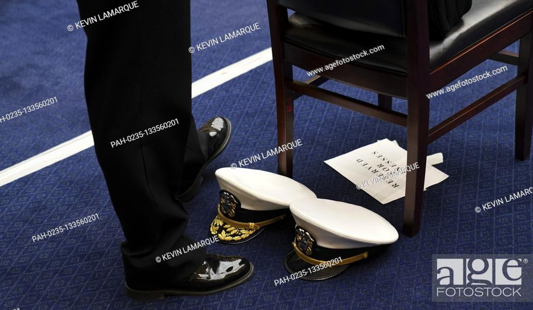 Photo de stock: The hats of Rear Admiral John P. Polowczyk, Vice Director, J4, Joint Staff and Admiral Brett Giroir, United States Assistant Secretary for Health sit on the.