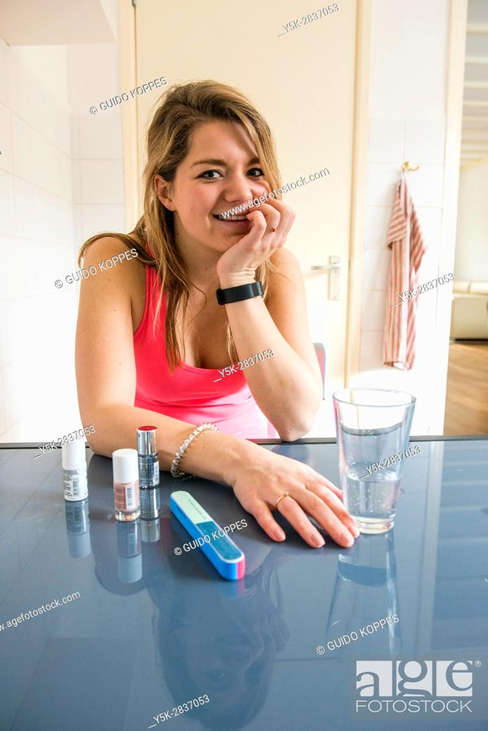 Stock Photo: Tilburg, Netherlands. Young adult girly woman doing her nales, while sitting at her kitchen table.