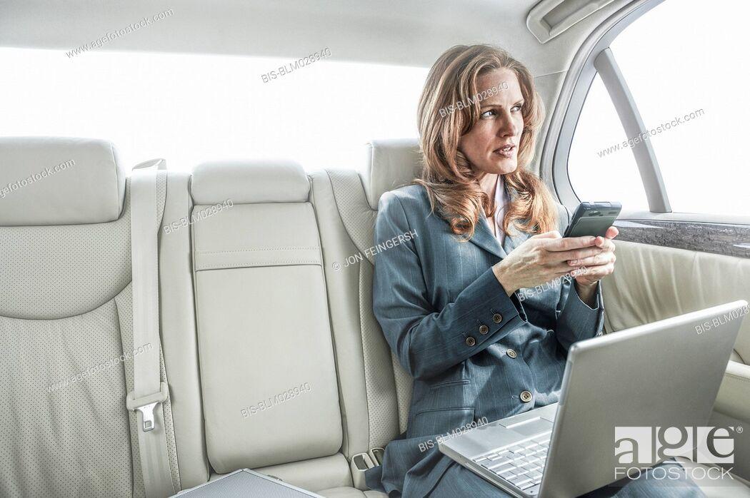 Imagen: Businesswoman working in backseat of car.