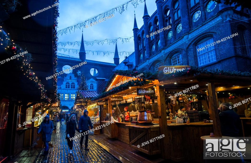 Stock Photo: During the continous rainfall, only few visitors walk the grounds of the Christmas market in Luebeck, Germany, 27 November 2017.