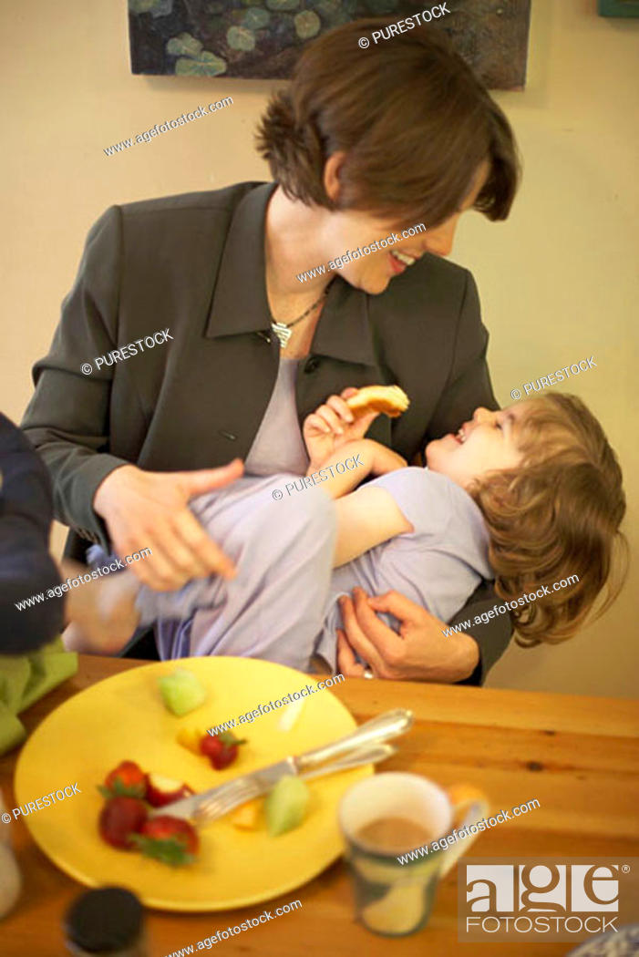 Stock Photo: Mid adult woman playing with her daughter at a dining table.