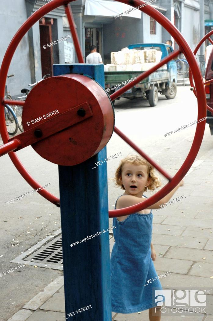 Stock Photo: Little girl playing in an old hutong in Beijing, China.