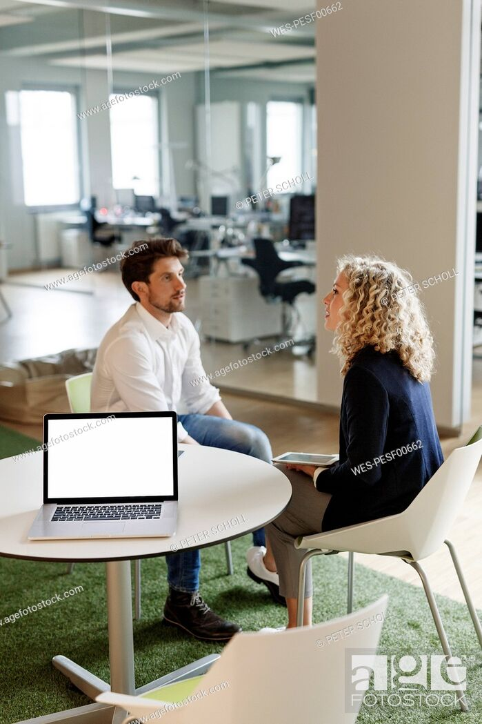 Stock Photo: Two colleagues talking in office with laptop on table.