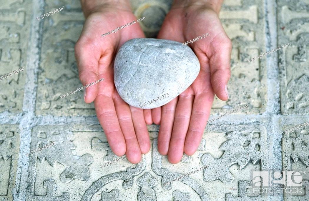 Stock Photo: Woman holding a Stone over an ornate Ground - Meditation - Element.