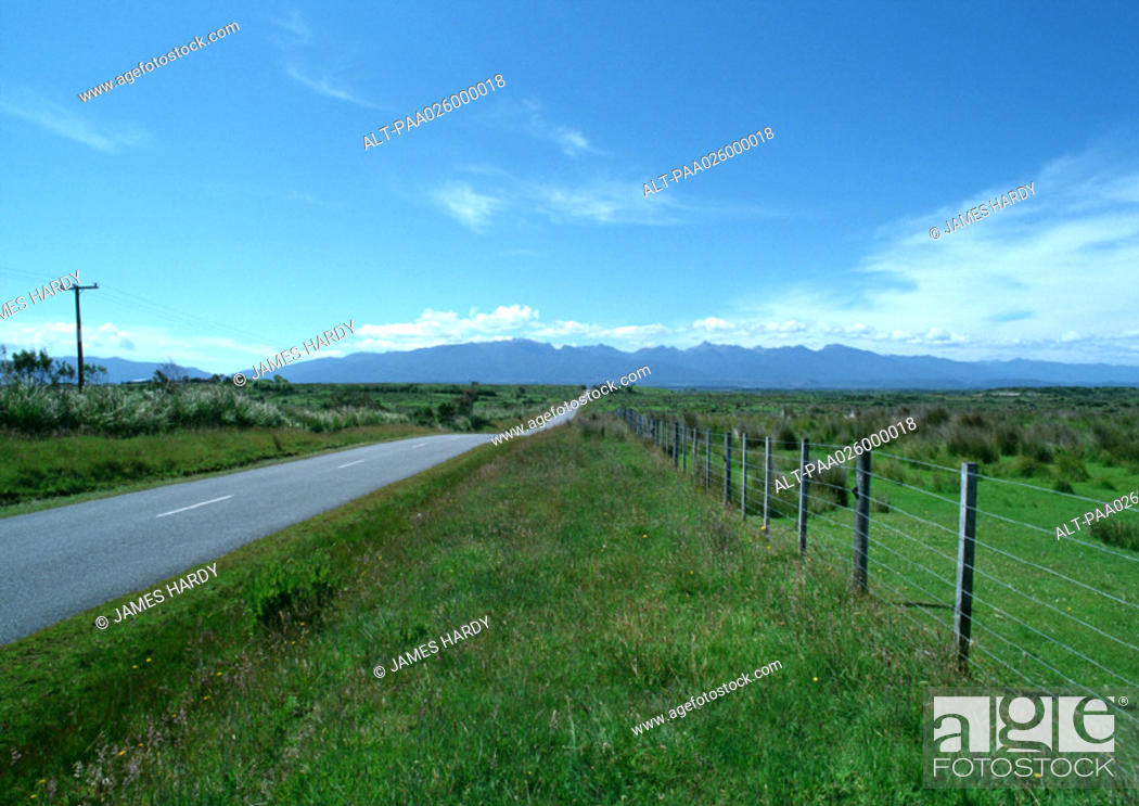 Stock Photo: New Zealand, road going through grassy rural area, mountain range in distance.