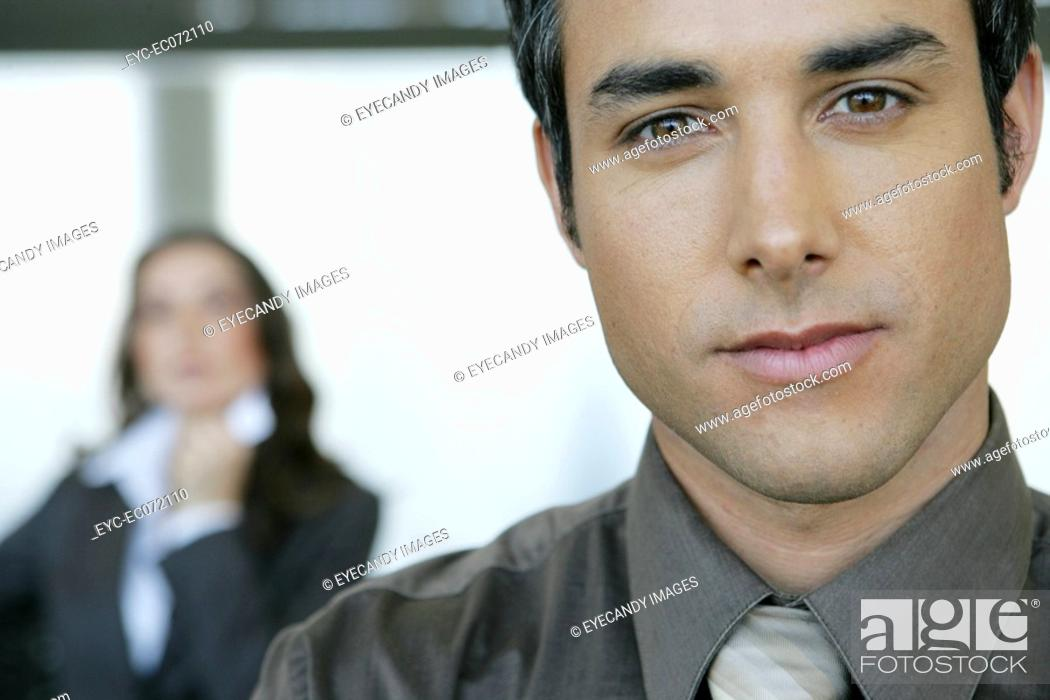 Stock Photo: Portrait of businessman in airport with businesswoman behind.