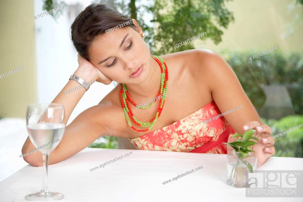 Stock Photo: Bored woman playing with plant at dining table.