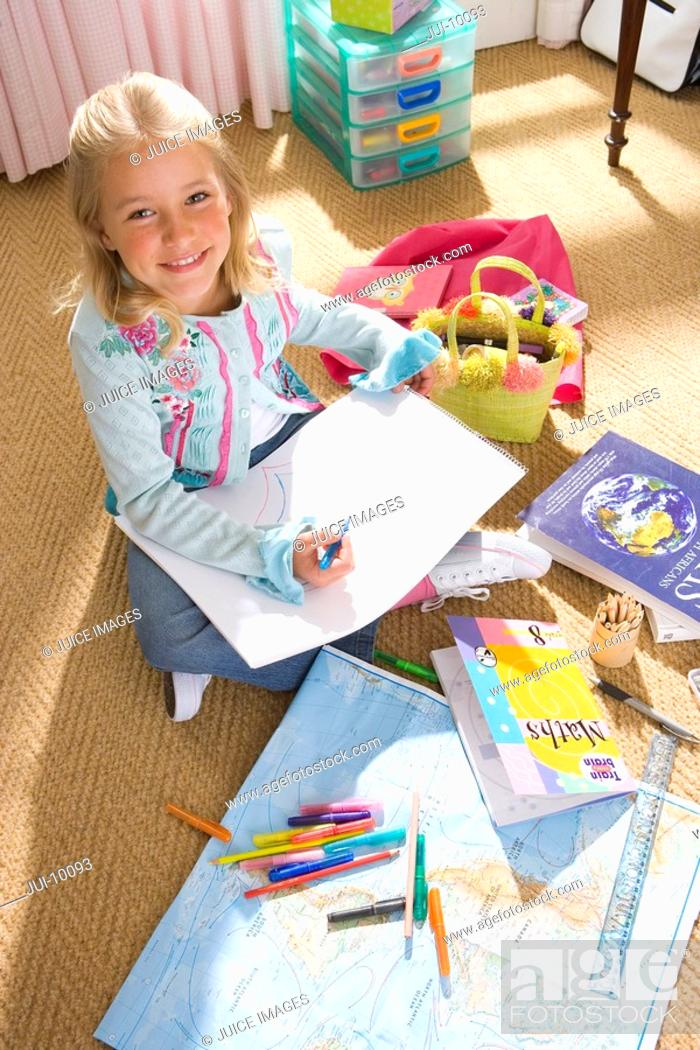 Stock Photo: Girl 8-10 drawing in bedroom, smiling, portrait, elevated view.