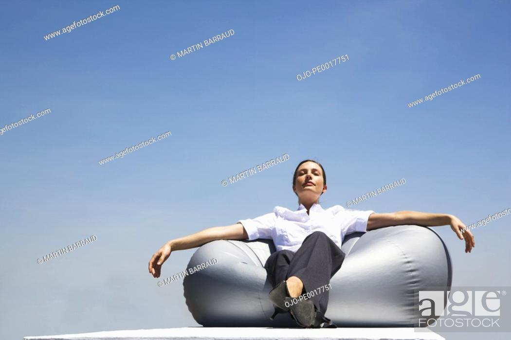 Stock Photo: Businesswoman sitting on beanbag chair outdoors with eyes closed.