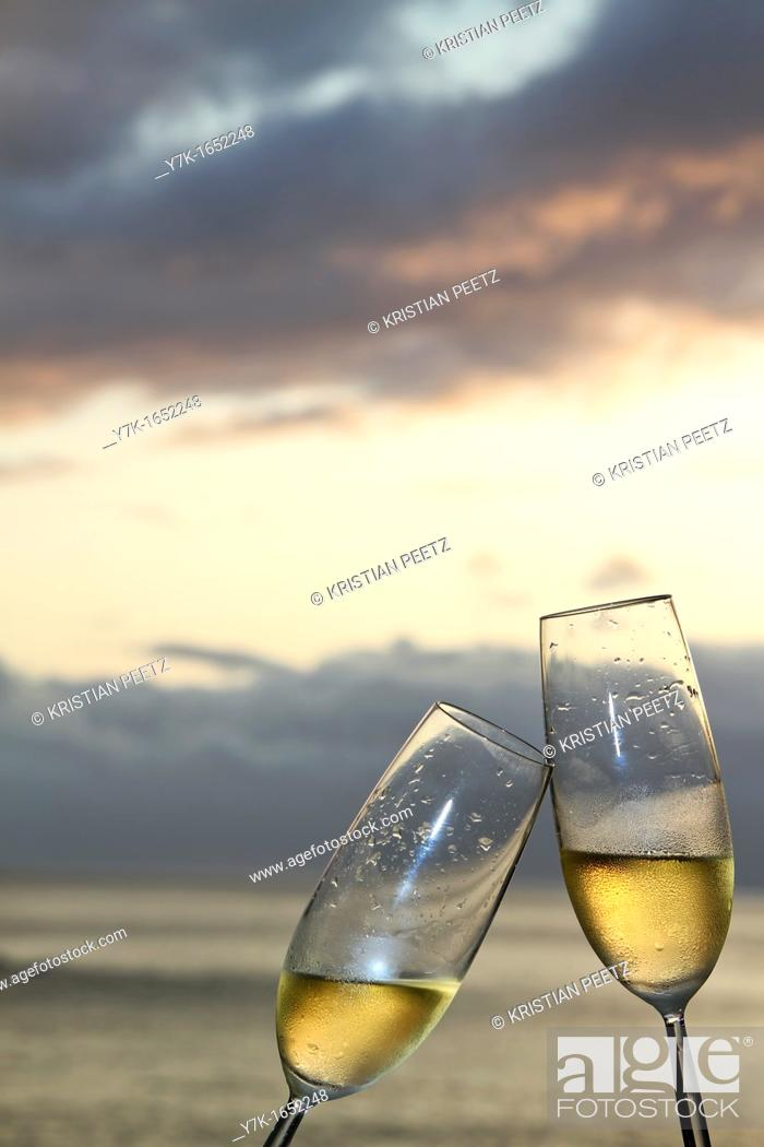 Stock Photo: Two champagne flutes toasting against ocean background.