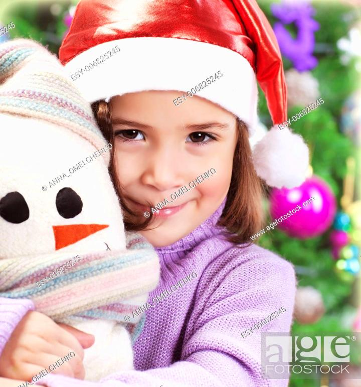 5149bd0d6de9 Stock Photo - Closeup portrait of cute little girl holding snowman soft toy  over Christmas tree background, wearing red Santa hat