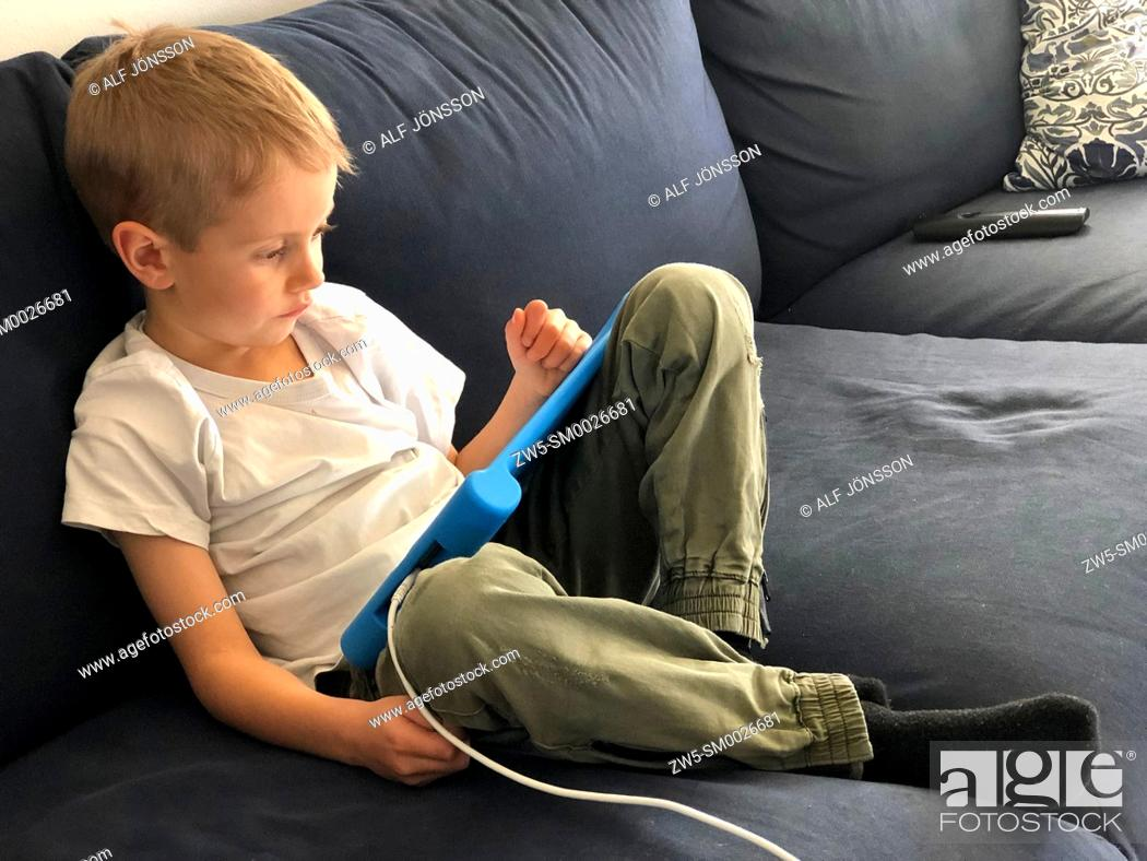 Stock Photo: Boy, five years old, lying with a tablet computer in Scania, Sweden.