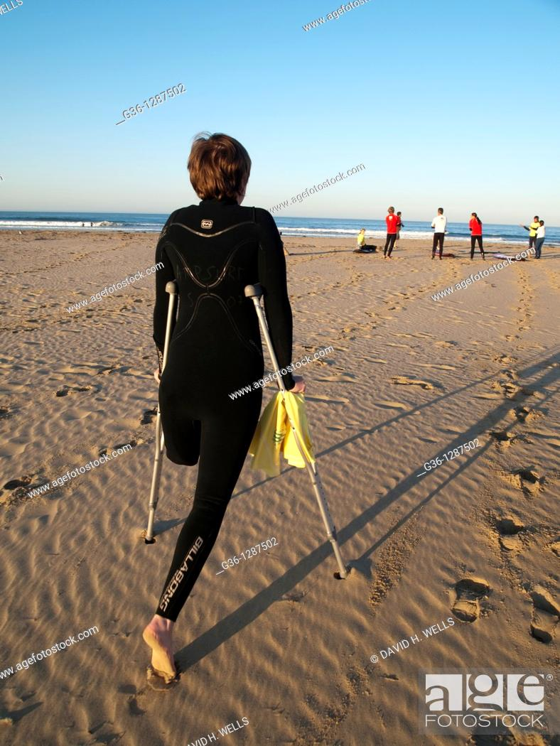 Stock Photo: In Pismo Beach, California, Courtney Wilson, who lost one leg to cancer as an adolescent, moves towards the shore to participate in one of the regular Surf.