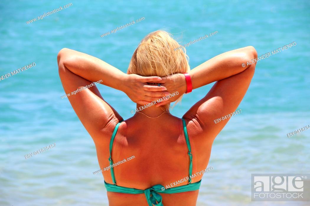 Imagen: Girl sunbathing in sun during vacation on background of azure sea. Woman enjoying relaxing at sea. Woman enjoying sun, freedom and life.