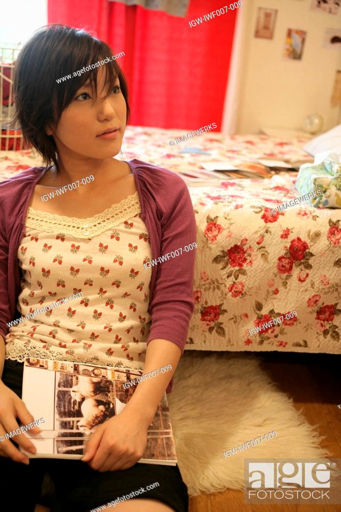 Stock Photo: A young woman holds a book as she sits near the bed.