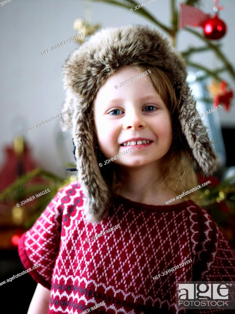 Stock Photo: Portrait of girl wearing fur hat, christmas tree in background.