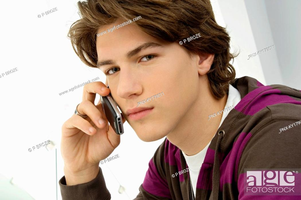 Stock Photo: Portrait of a teenage boy talking on a mobile phone.