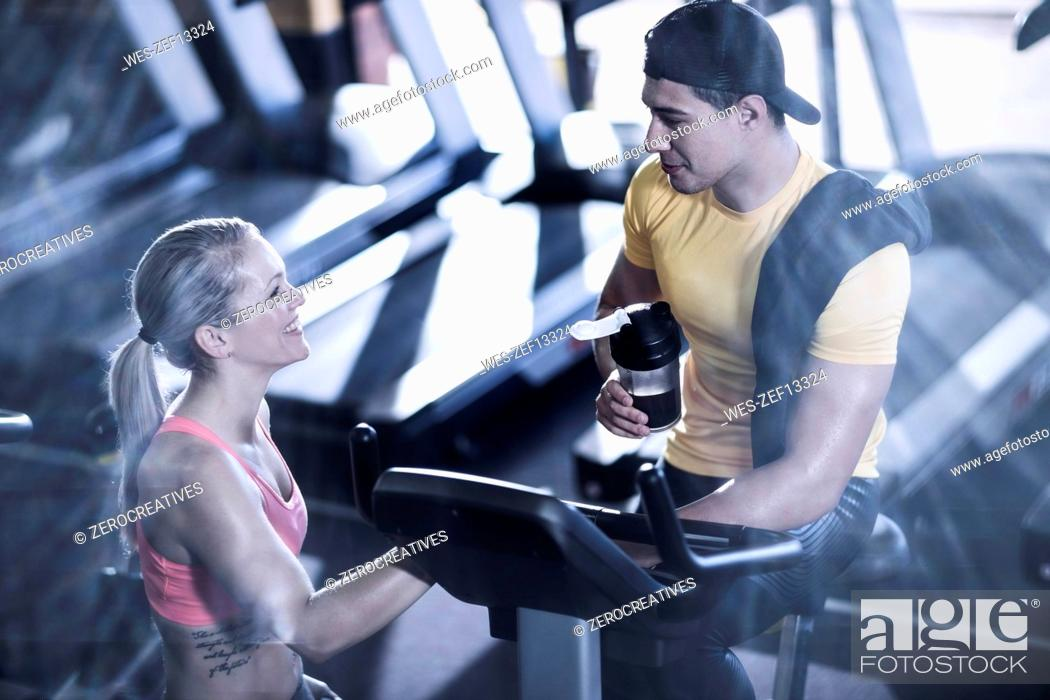 Stock Photo: Young man and woman talking in gym.