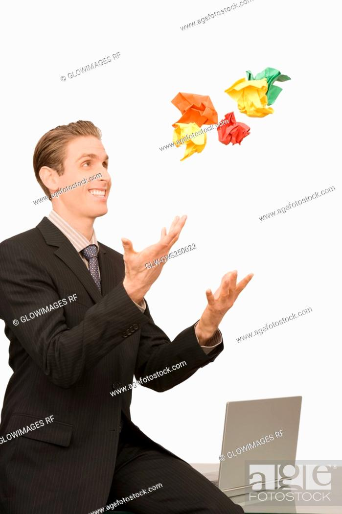 Stock Photo: Businessman throwing crumpled papers.