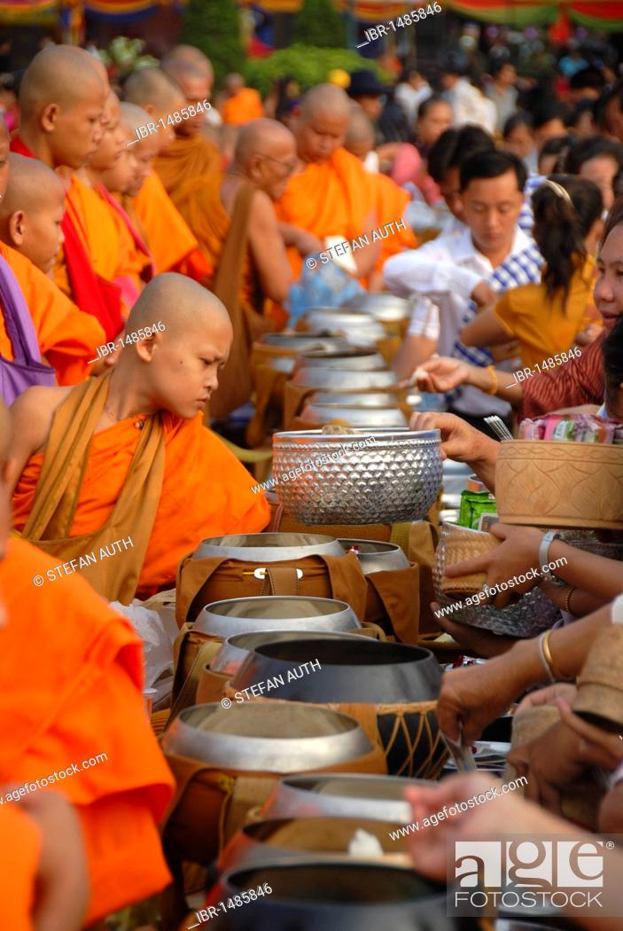 Stock Photo: Theravada Buddhism, That Luang Festival, Tak Bat, monks standing behind alms bowls, hands, believers, pilgrims giving alms, orange robes, Vientiane, Laos.