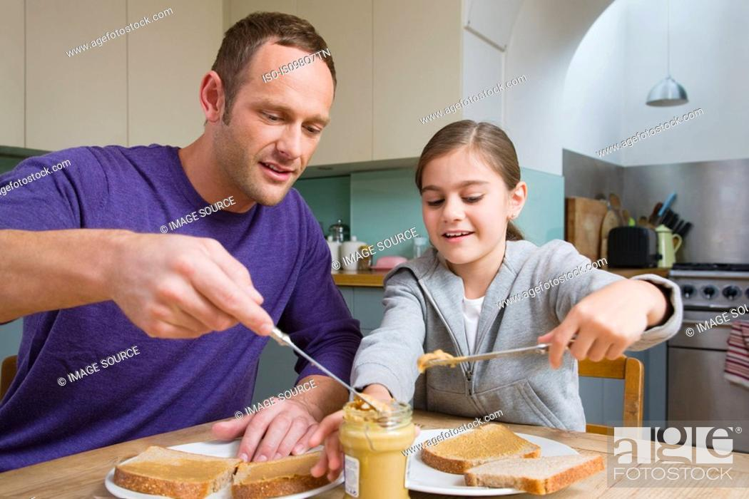 Stock Photo: Father and daughter making sandwiches.