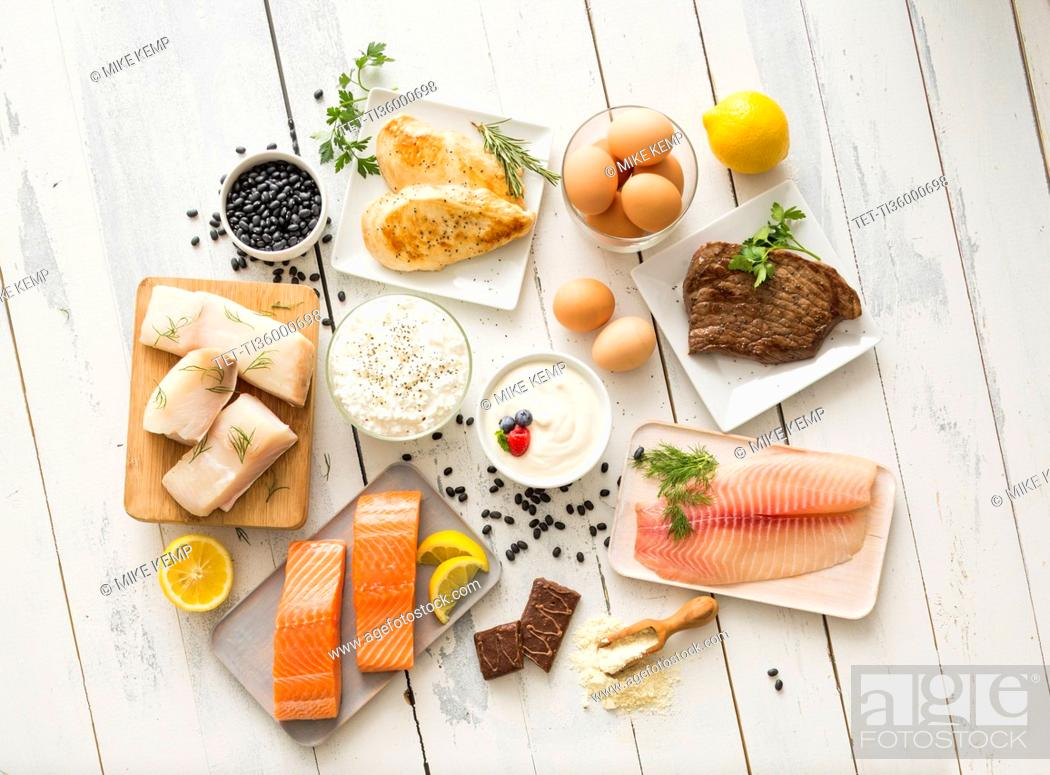 Photo de stock: Chicken meat, fish, cottage cheese, yogurt and eggs on white table.