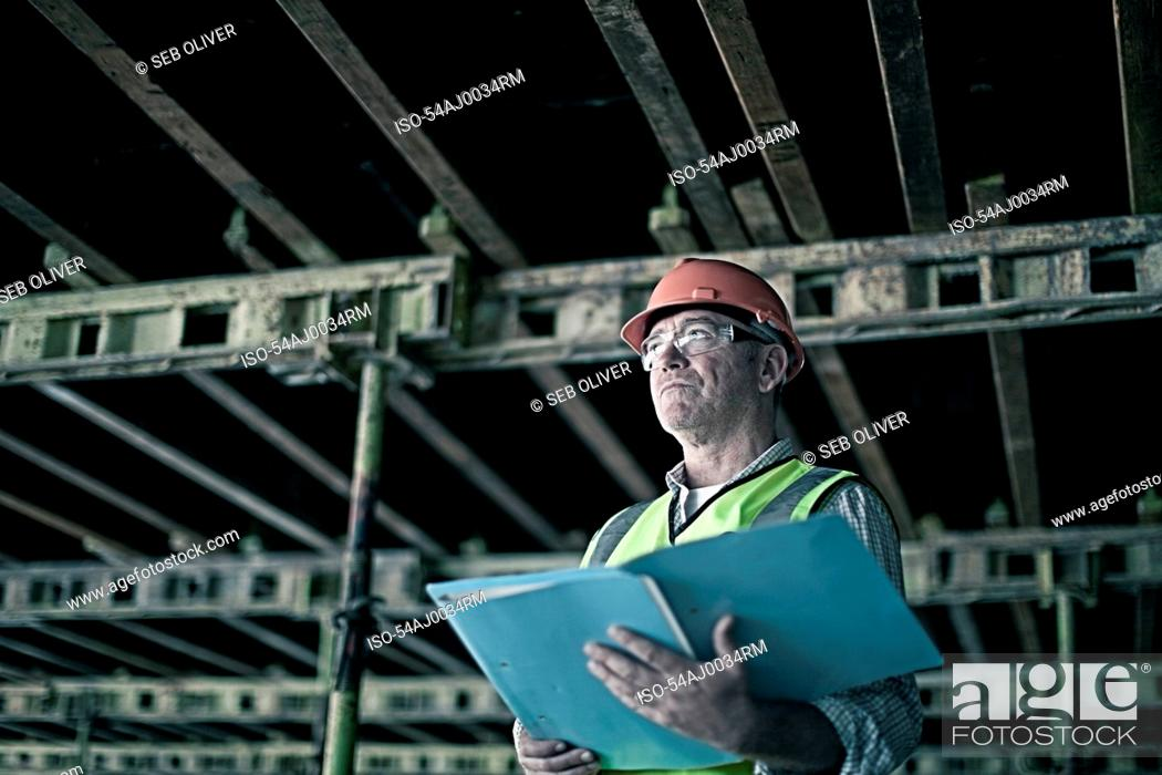 Stock Photo: Construction worker reading blueprints.