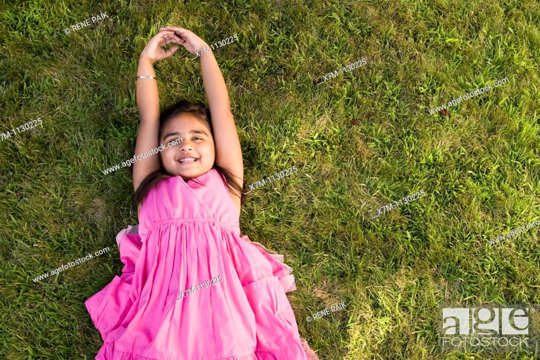 Stock Photo: A little Indian girl relaxing on the grass.