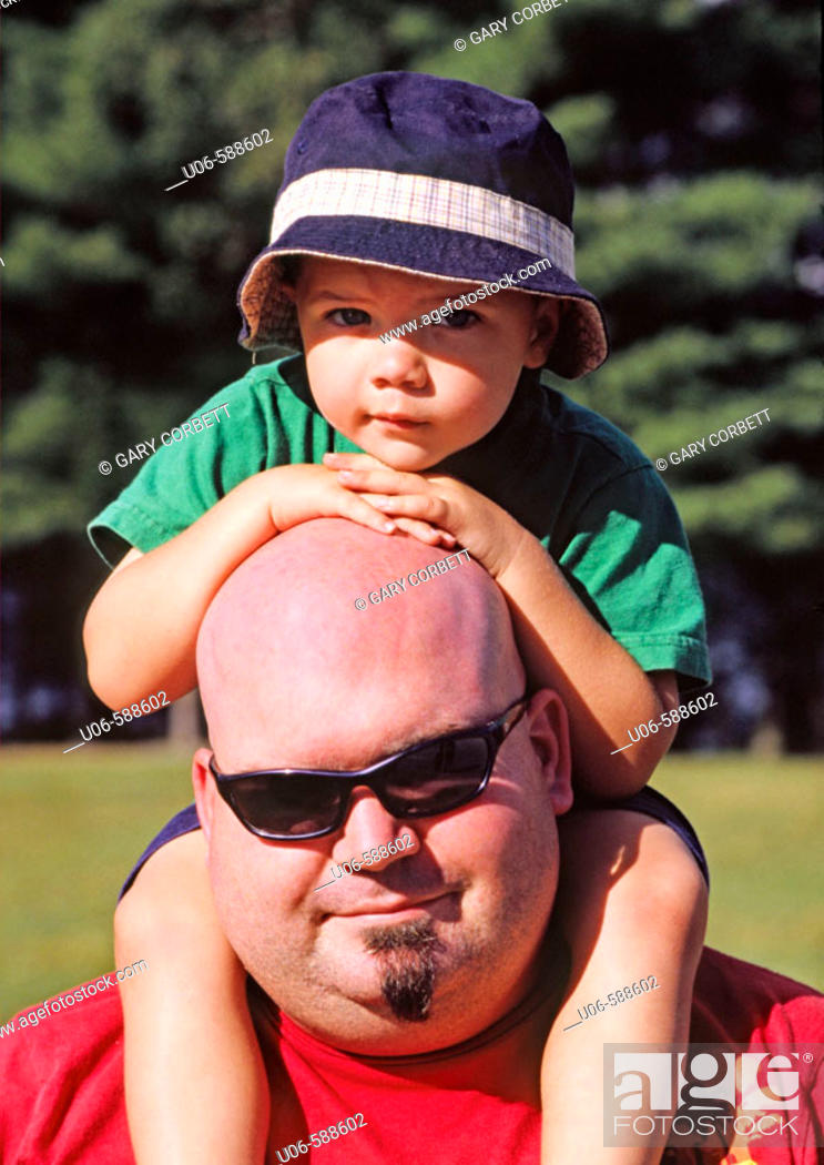 Stock Photo: 3 yr old boy sitting on fathers shoulders.