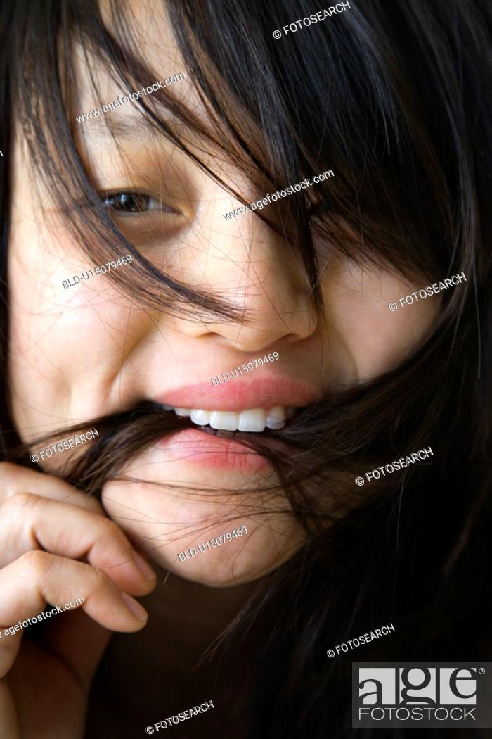 Stock Photo: Close up portrait of pretty young Asian woman biting her hair.