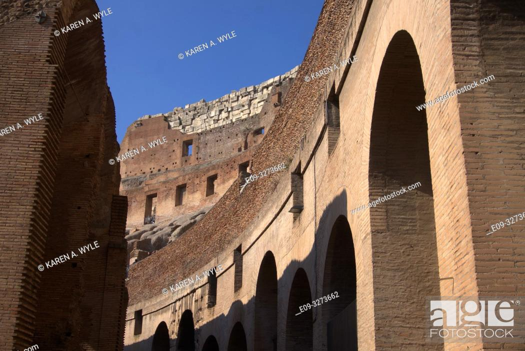 Stock Photo: inside of Colosseum, including rebuilt section of wall, on sunny day with blue sky, Rome, Italy.
