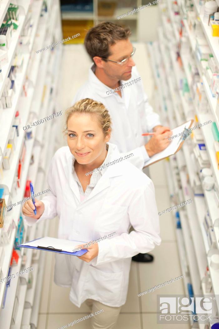 Stock Photo: Pharmacists browsing medicines on shelf.