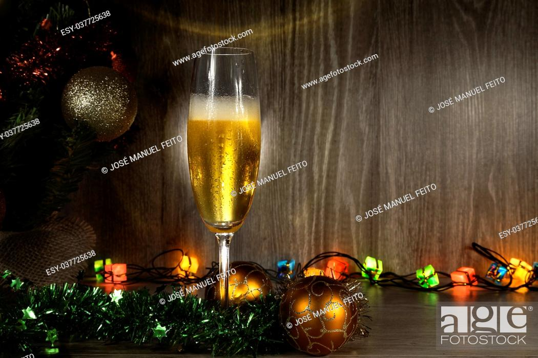 Stock Photo: champagne glass with Christmas balls, Christmas lights and tree wooden background.
