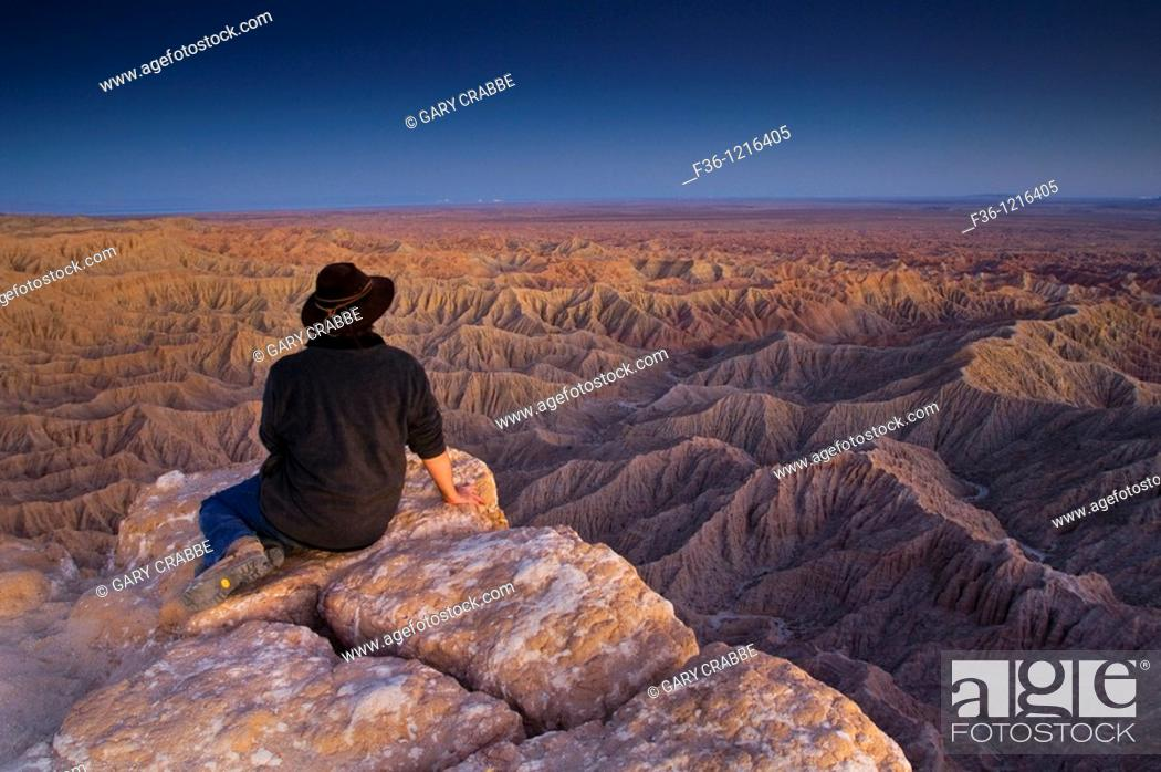 Stock Photo: Tourist enjoying a quiet evening overlooking eroded hills of the Borrego Badlands, Fonts Point, Anza Borrego Desert State Park, San Diego County, California.