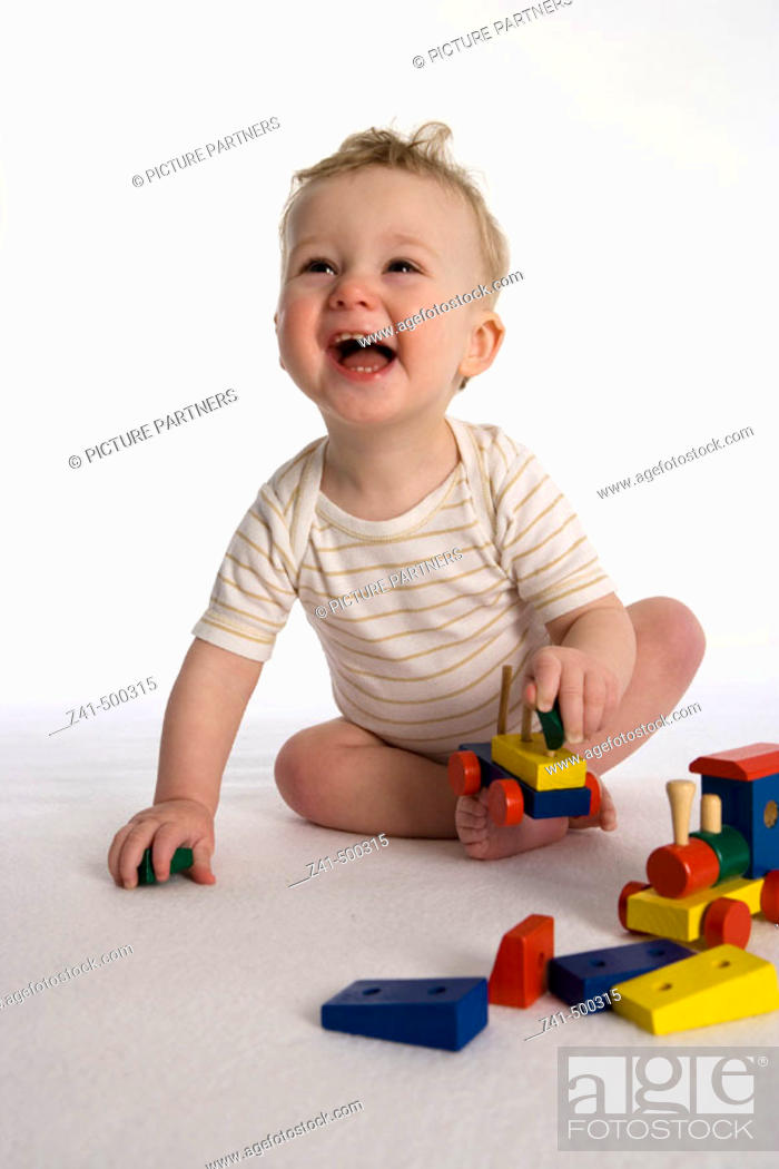 Stock Photo: Little boy playing with a wooden train.