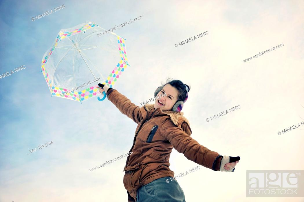 Stock Photo: Portrait of smiling young woman holding umbrella.