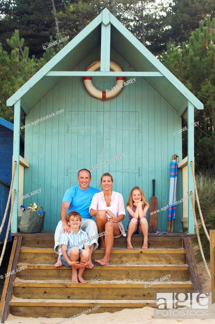 Stock Photo: Vacationing Family sitting in beach hut portrait.