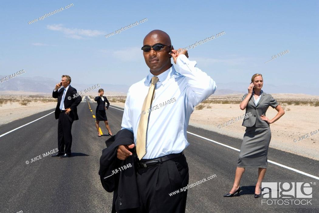 Stock Photo: Small group of businessmen and women using mobile phones on road in desert, low angle view.