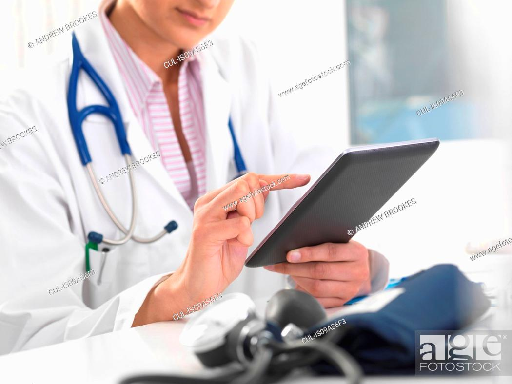 Stock Photo: Cropped shot of female doctor using digital tablet touchscreen to update medical records.