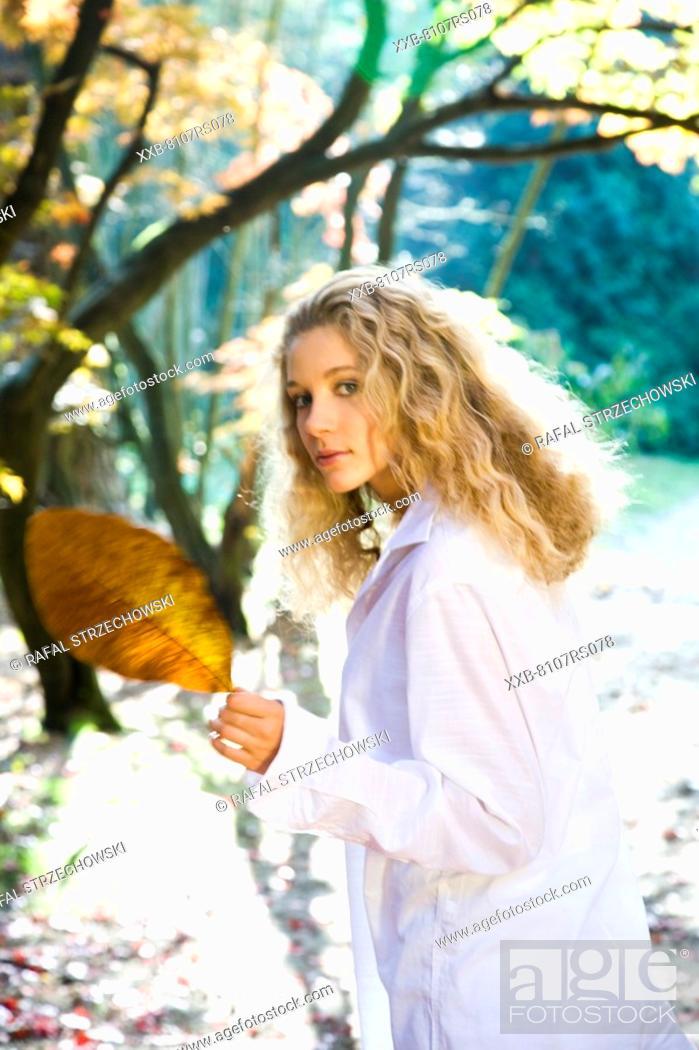 Stock Photo: Autumn portrait of woman in white shirt.