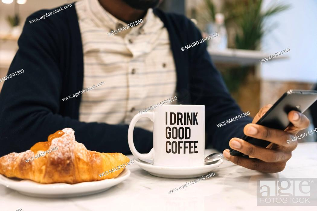 Stock Photo: Close-up of man with croissant and cup of coffee in a cafe using cell phone.