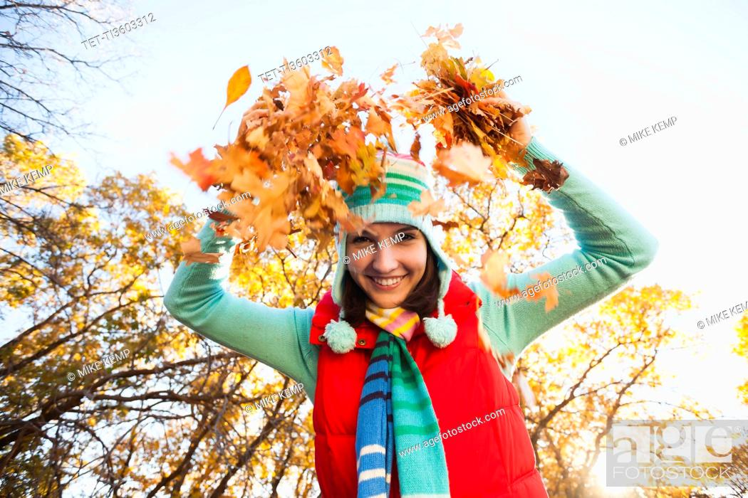 Stock Photo: Portrait of smiling young woman throwing dry leaves in autumn forest.