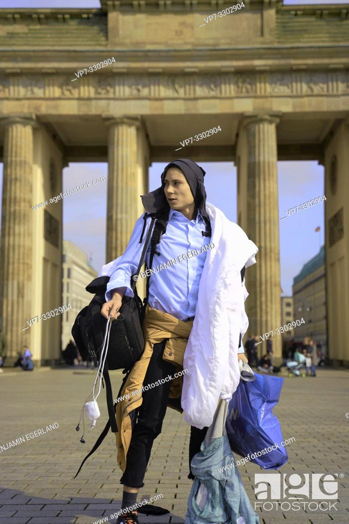 Stock Photo: young tourist man, traveller, carrying too much baggage, in front of touristic sight Brandenburg Gate, in Berlin, Germany.