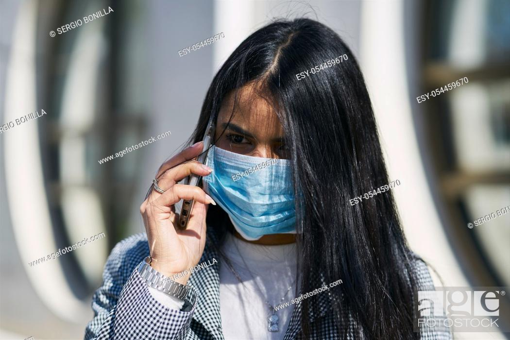 Photo de stock: Girl with a mask to avoid contagion walking down the street. Coronavirus concept.