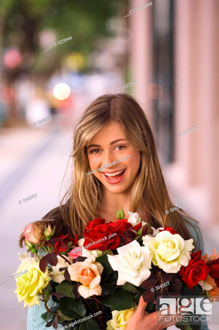 Stock Photo: Young woman holding roses outdoors.