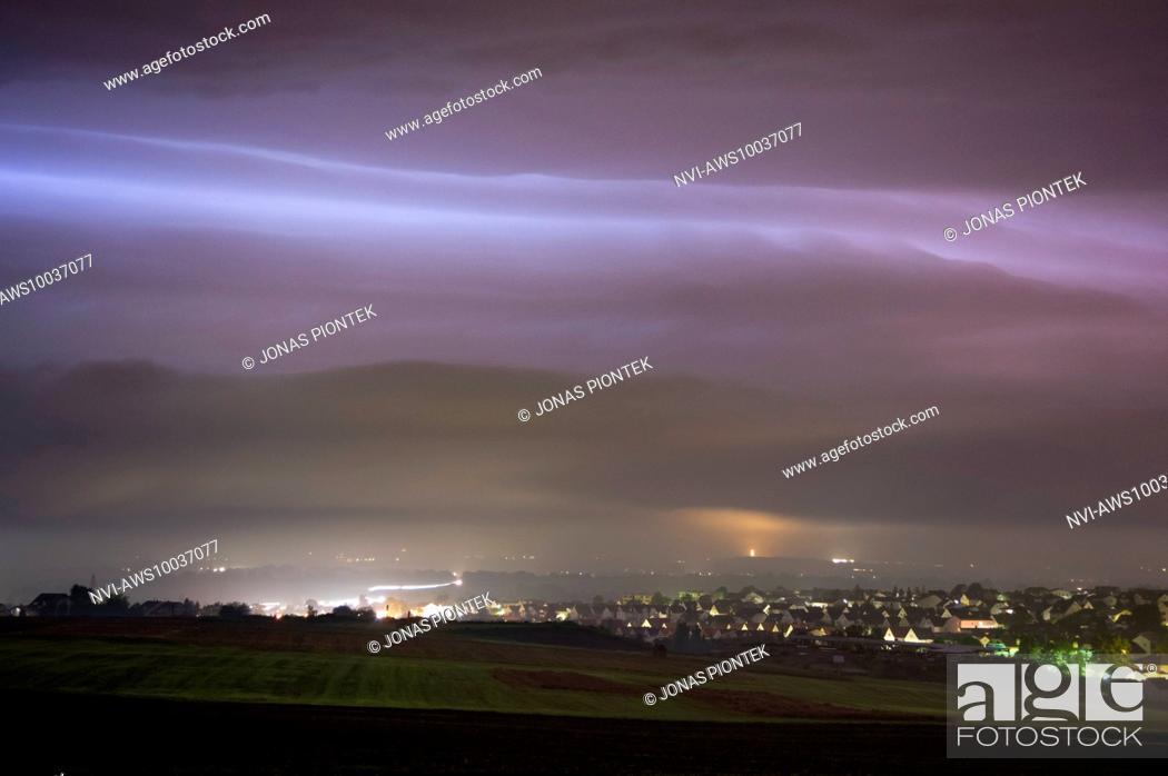 Stock Photo: Nighttime shelf cloud of a sheet lightning illuminated, dying thunderstorm behind Langgöns, Hessia, Germany.